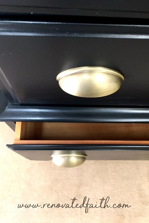 black dresser with gold hardware